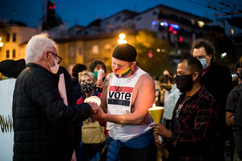 Stephan Ferris lights a candle for Cleve Jones during a vigil to honor the life of Ruth Bader Ginsburg in the Castro on Sep. 18, 2020.