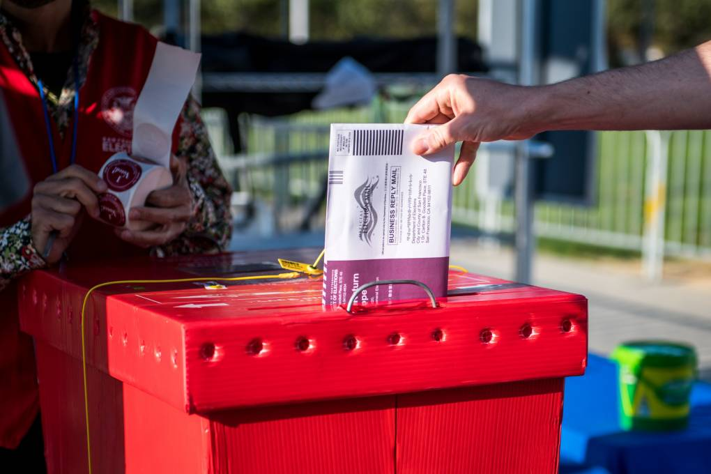 A voter drops off a ballot at a new outdoor voting center near Civic Center Plaza in San Francisco on Oct. 5, 2020, the first day of early voting. Beth LaBerge/KQED