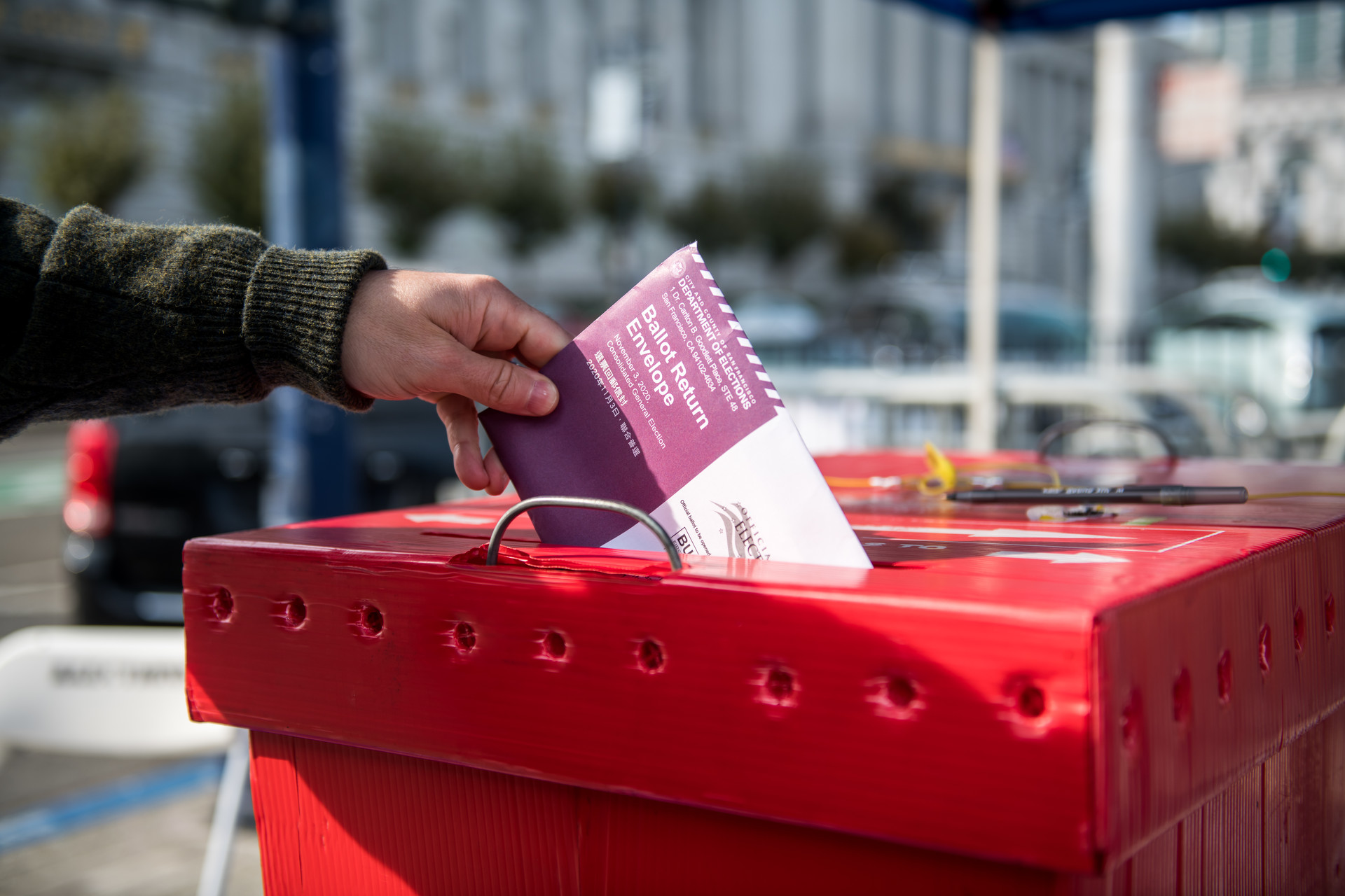 Hand holding ballot drops it in red cardboard ballot box