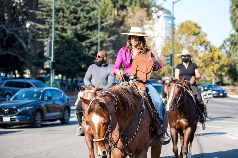 Brianna Noble (front), Dale Johnson (L) and Rachel Royce (R) ride their horses to the Alameda County Courthouse in Oakland to drop off their mail-in ballots as part of a Ride Out to Vote event on Oct. 29, 2020.