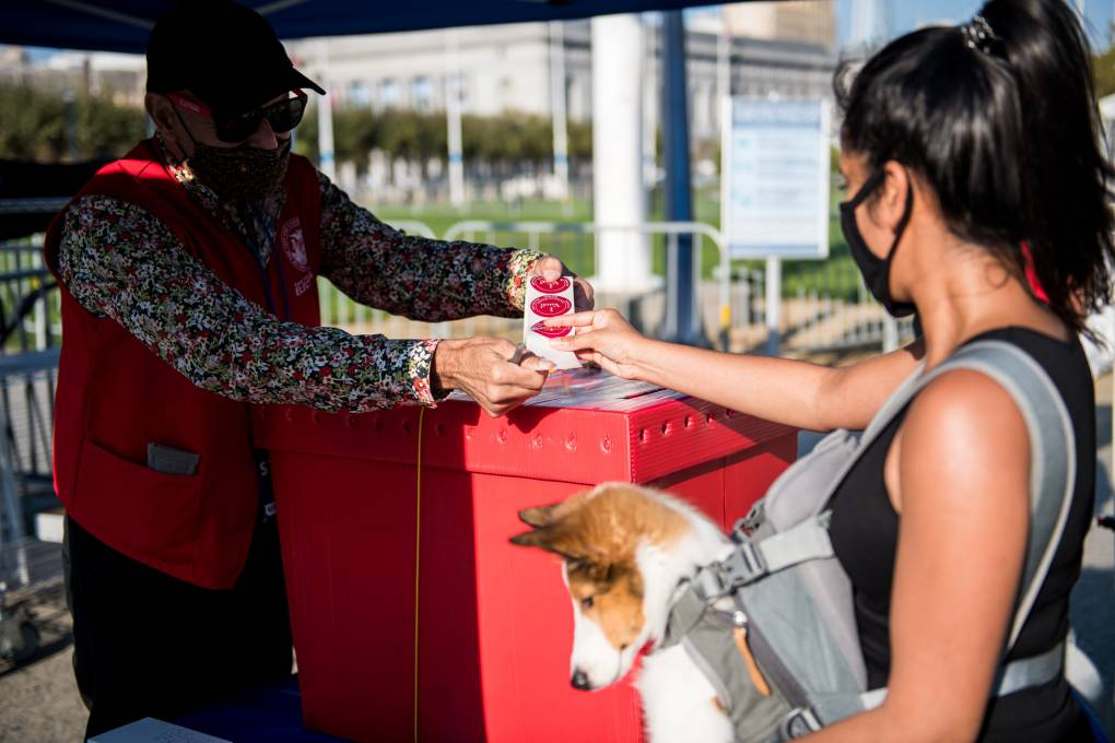 "A voter receives an ""I Voted"" sticker at a new outdoor voting center near Civic Center Plaza in San Francisco on Oct. 5, 2020, the first day of early voting."