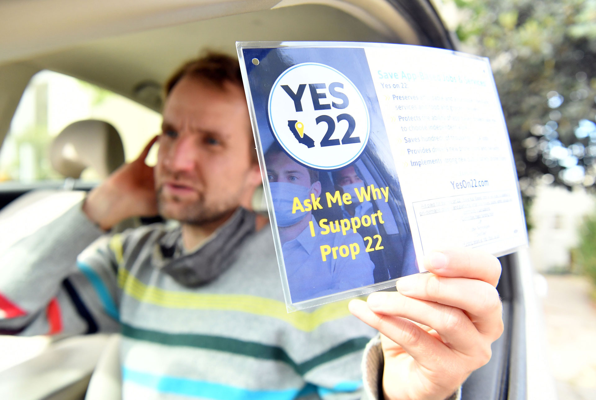 Uber driver Sergei Fyodorov holds a flyer supporting a yes vote on Proposition 22 in Oakland.