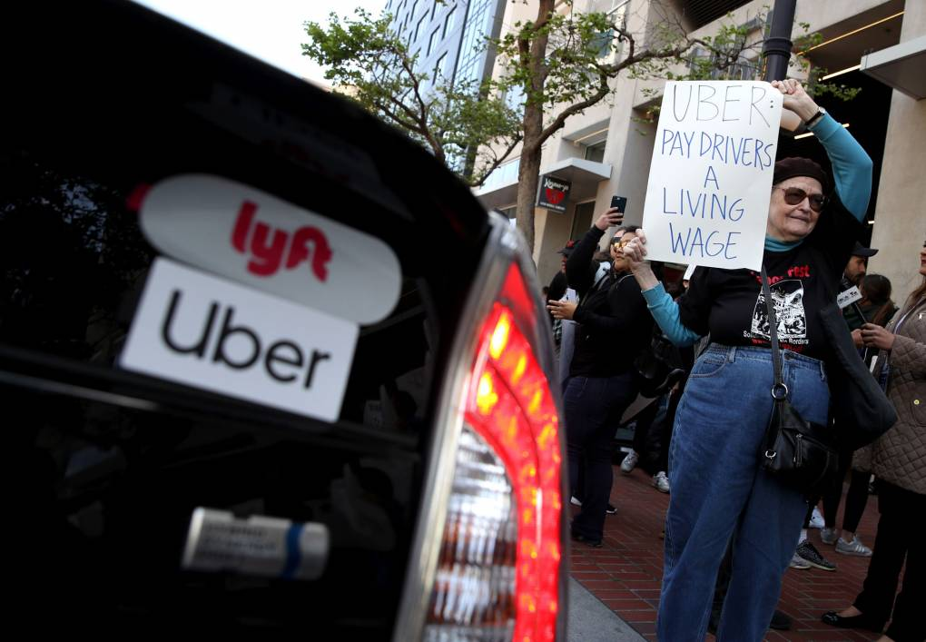 A supporter of ride-hail drivers holds a sign during a protest in front of Uber headquarters in May, 2019. Prop. 22, backed by huge amounts of cash from gig companies, would create a new class of worker in California. Justin Sullivan/Getty Images