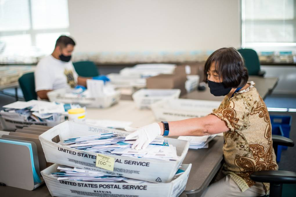 A woman in short sleeves and a mask sits at a fold-out table in front of baskets of mail.