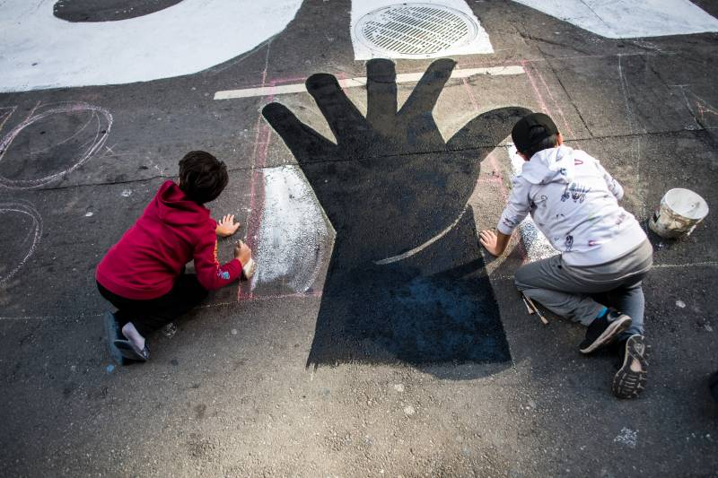 "Two children help paint a part of a street mural that reads ""Hands Off Our Ballots"" on Montgomery Street in San Francisco on Nov. 6, 2020."