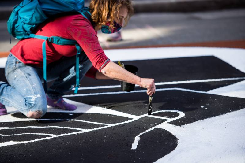 A woman paints a hand placing a ballot into a ballot box as part of a mural that stretches across one block of Montgomery Street in San Francisco on Nov. 6, 2020.