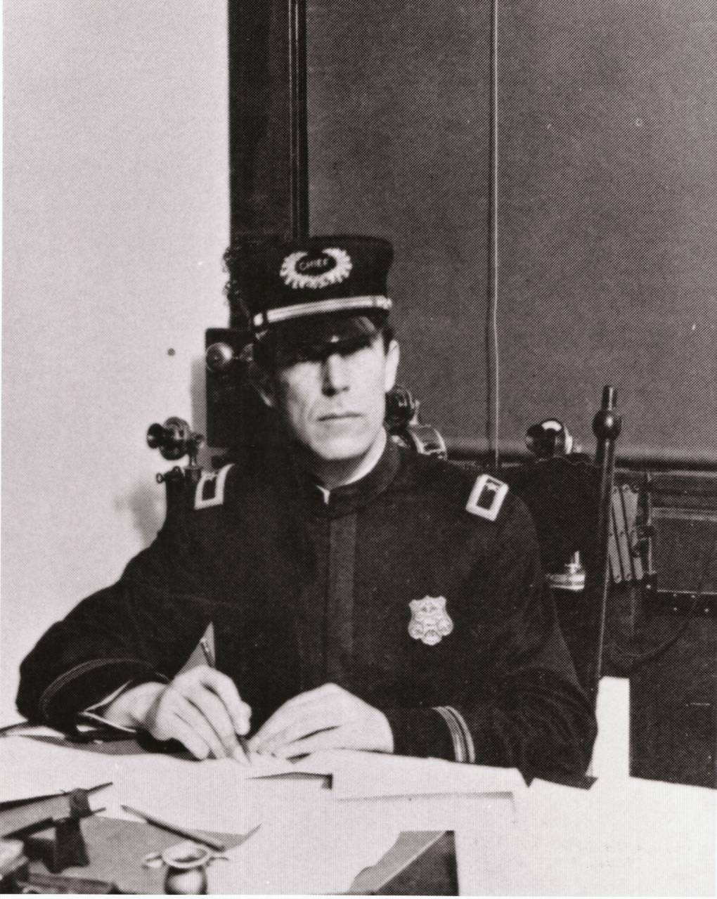Portrait of August Vollmer sitting at his desk wearing a dark uniform and his chief's hat.