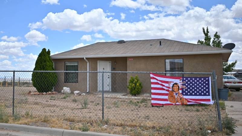 An American flag with an image of a Native American printed on it is attached to a fence outside a home in the East To'Hajiilee housing community amid the spread of the coronavirus on May 25, 2020 in To'Hajiilee Indian Reservation, New Mexico.
