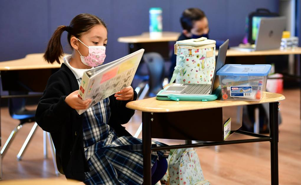 First grade students prepare for class at St. Joseph Catholic School in La Puente, California on November 16, 2020, where pre-kindergarten to second grade students in need of special services returned to the classroom for in-person instruction.