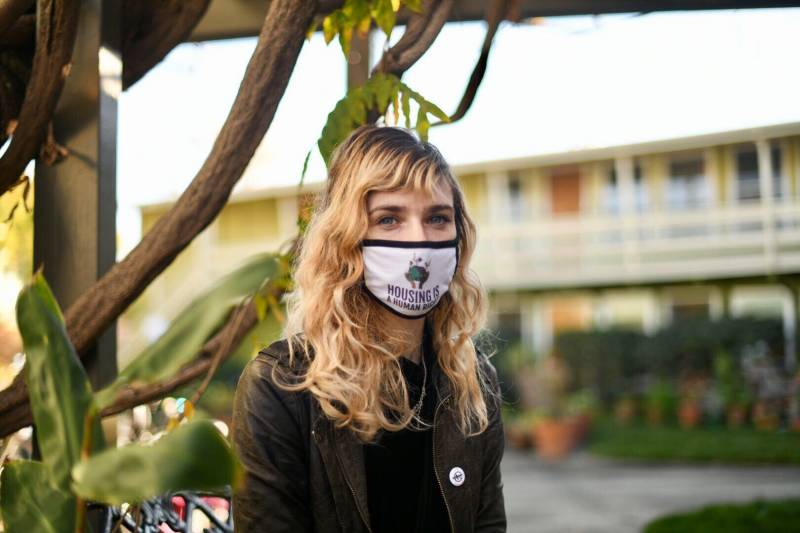 A woman standing in front of apartments, wearing a mask that reads 'housing is a human right'