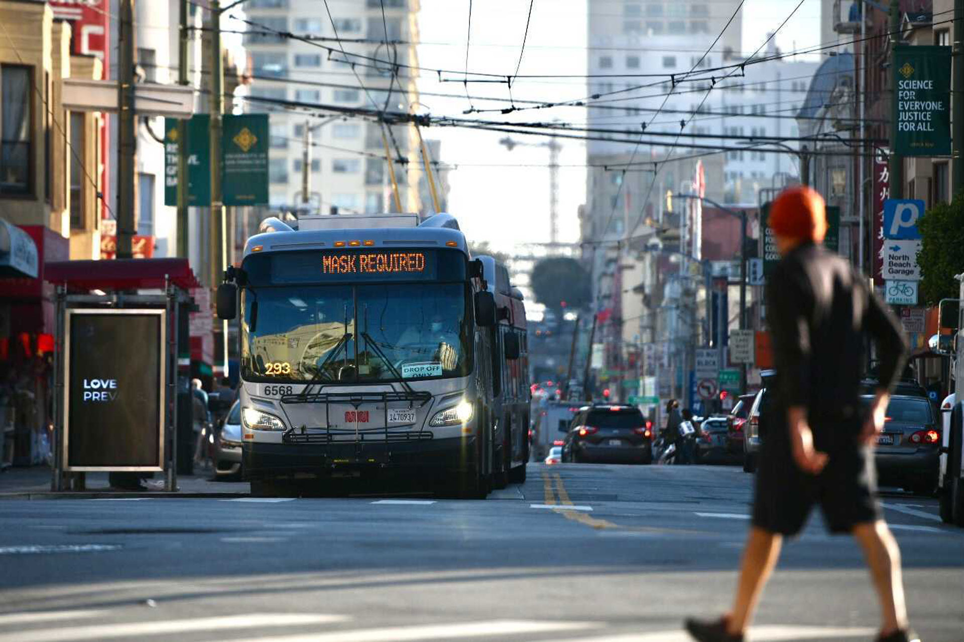 Pedestrian walks in North Beach, bus in the background