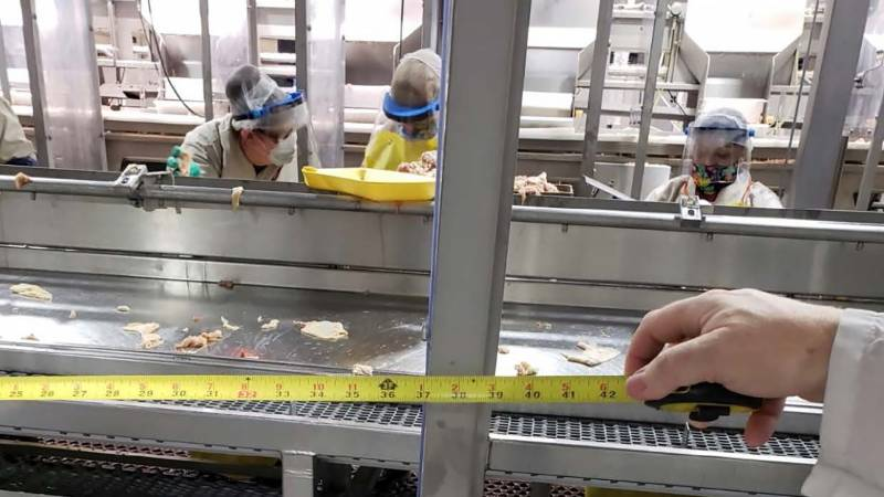 Workers standing near each other at a Foster Farms assembly line in Livingston.