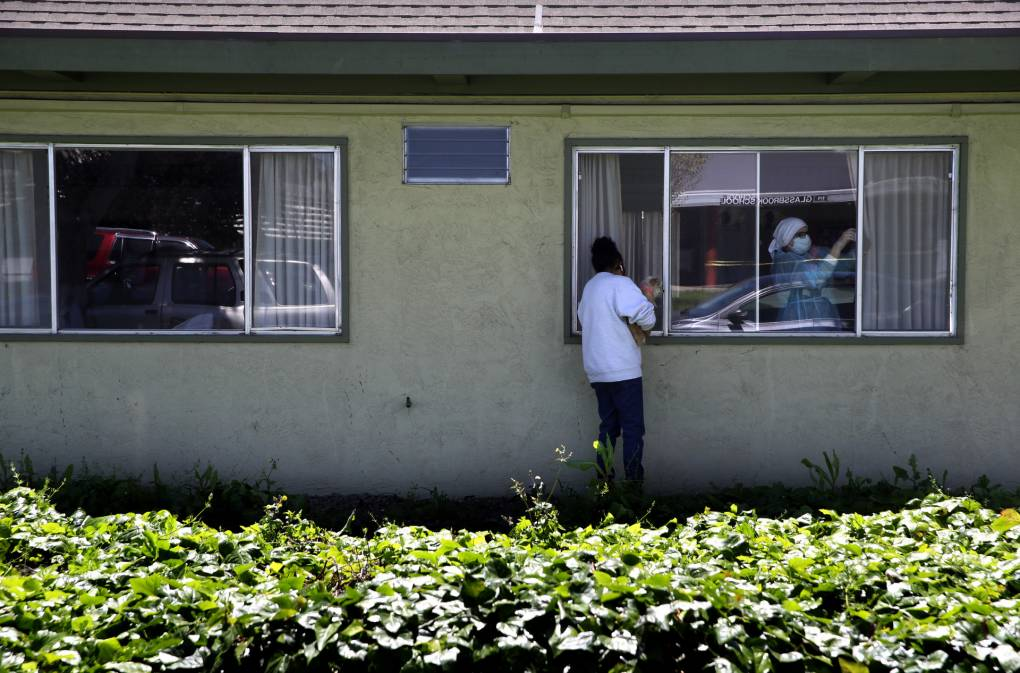 HAYWARD, CALIFORNIA - APRIL 14: Adrina Rodriguez holds her dog as she looks through a window while visiting her father who is a patient at the Gateway Care and Rehabilitation Center that has tested negative for COVID-19 on April 14, 2020 in Hayward, California. The Gateway Care and Rehabilitation Center remains open after a tenth patient died from COVID-19 complications.