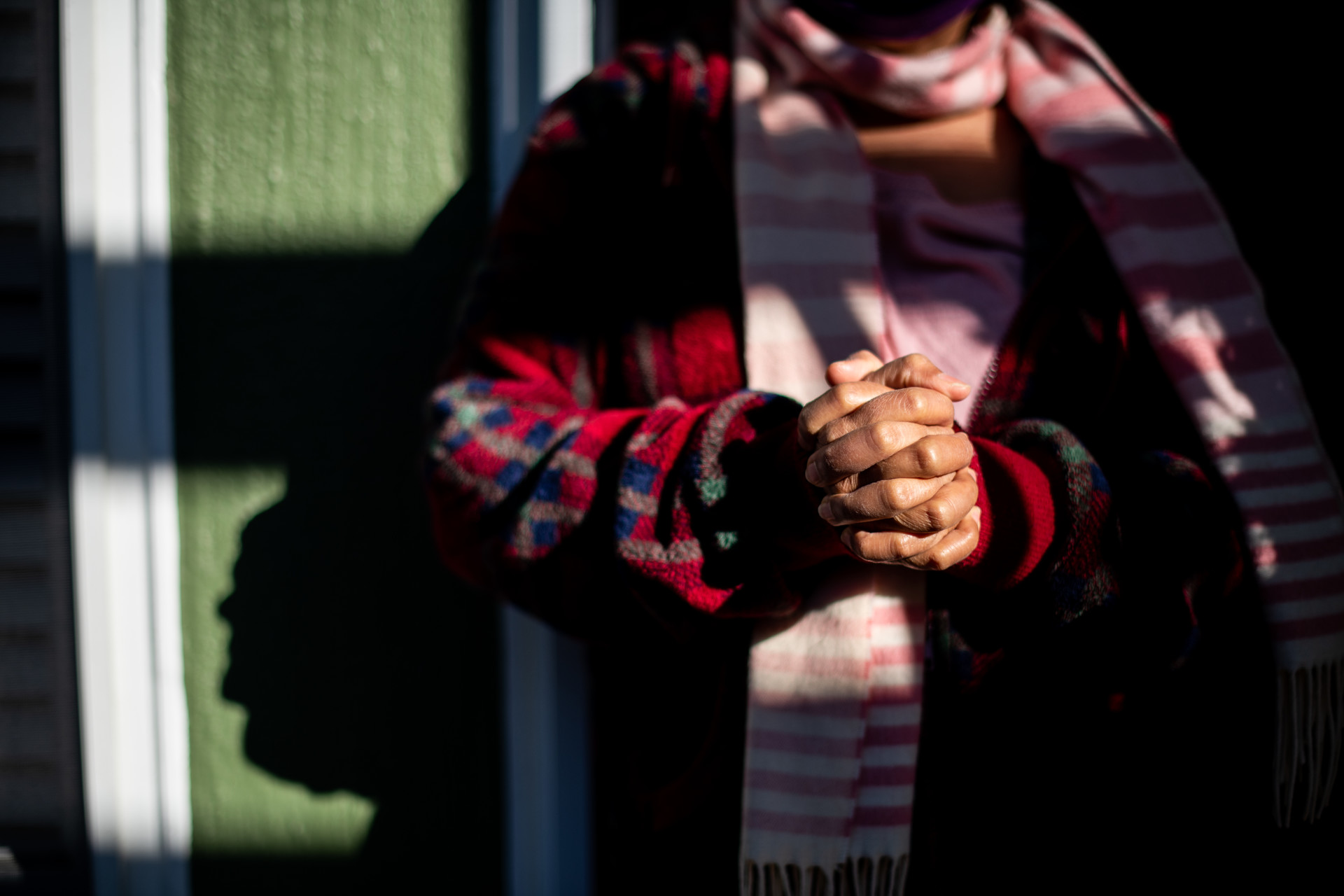 A person standing outside of an apartment building, clasping their hands together