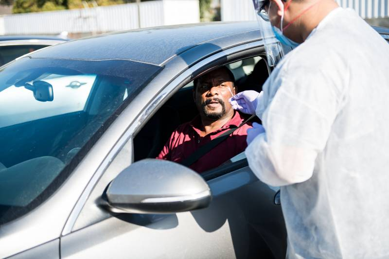 Phlebotomy tech Brandon Tran administers a COVID-19 swab test to Herb Sanders in his car at a COVID-19 testing pop-up site by Umoja hosted by Acts Full Gospel Church in Oakland on Oct. 31, 2020. Umoja's mission was to get more African Americans in Oakland to get tested for the coronavirus as well as to present a more accurate picture of positivity rates in the Black population.