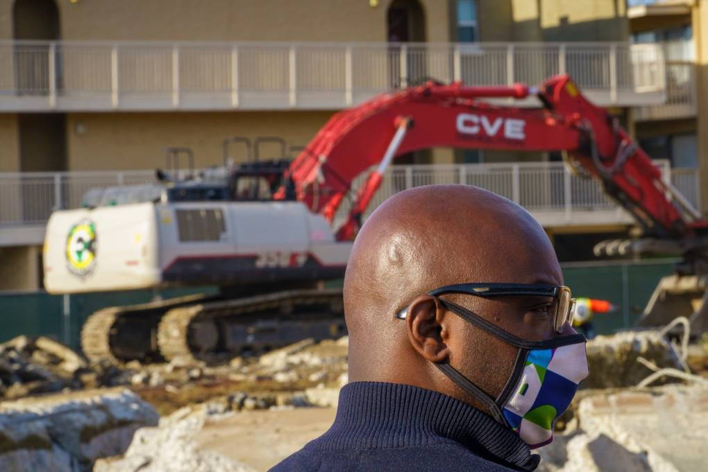 Man wearing mask observing construction work