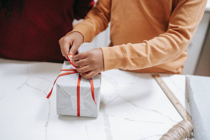 A pair of hands wrapping a white holiday gift box with red ribbon