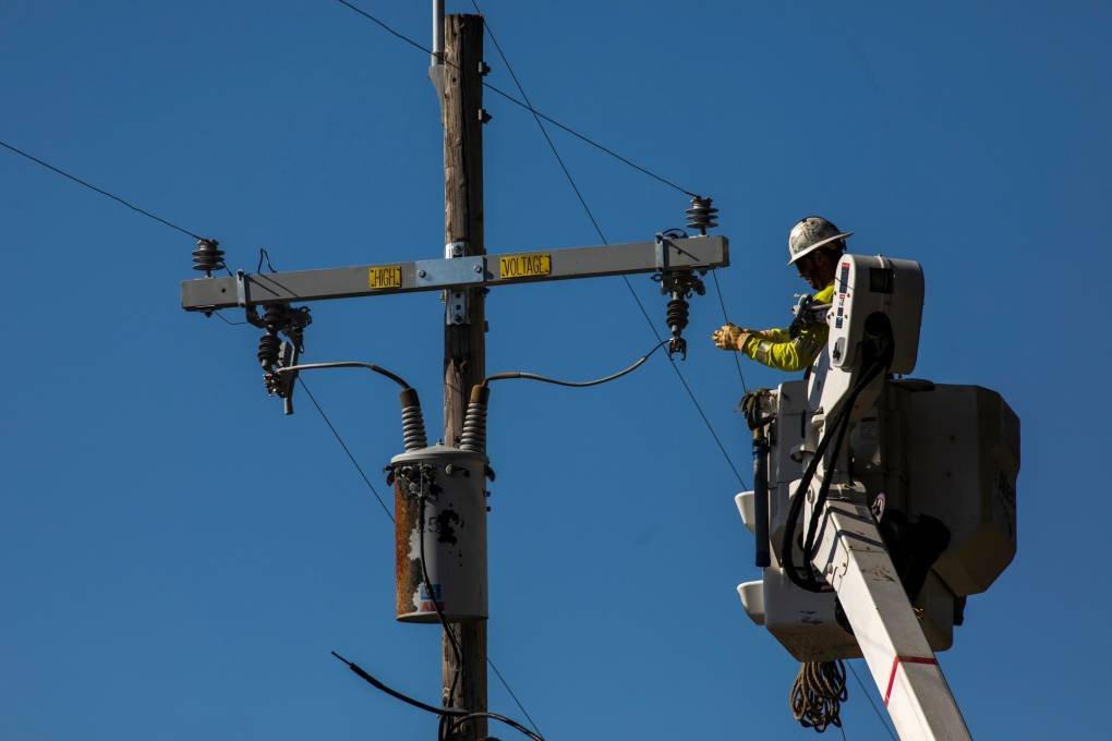 A PG&E contractor works on utility poles along Highway 128 near Geyserville, California on October 31, 2019.
