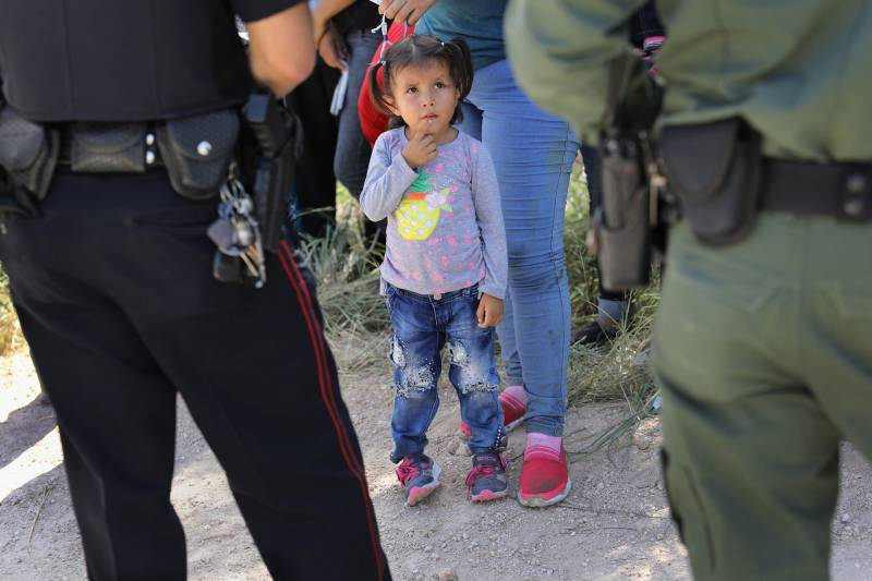 child looks up at CBP agents