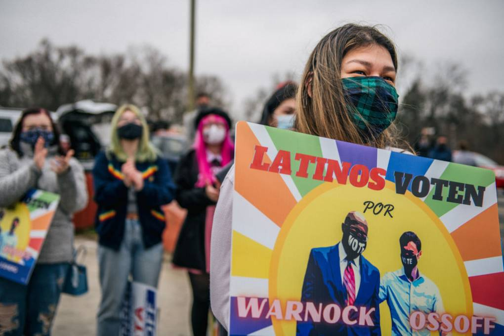 A woman holds a sign during a Latino meet and greet and literature distribution rally on December 30, 2020 in Marietta, Georgia. In the lead-up to the January 5 runoff election, Democratic Senate candidate Jon Ossoff continues to focus on early voting efforts across metro Atlanta.