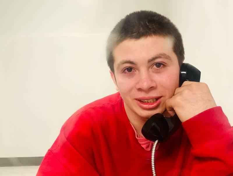 Juan Jose Erazo Herrera speaks to a visitor on a ICE detention center phone