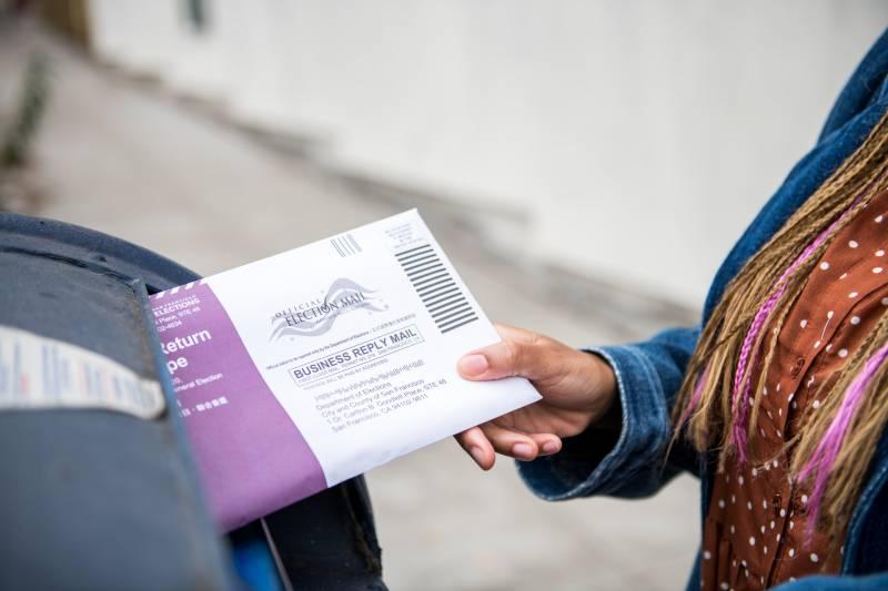 A hand slides a ballot into a blue postal box.