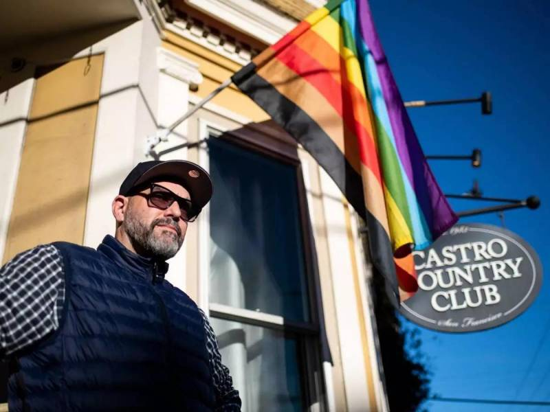 A man in sunglasses and a hat stands beneath a Pride flag outside a Victorian with a sign that says Castro Country Club.