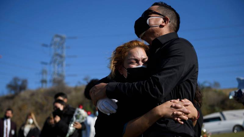 Maricela Arreguin Mejia (L) and her brother Nestor Arreguin mourn the death of their father Gilberto Arreguin Camacho, 58, due to COVID-19 during his burial at a cemetery on New Year's Eve, December 31, 2020.