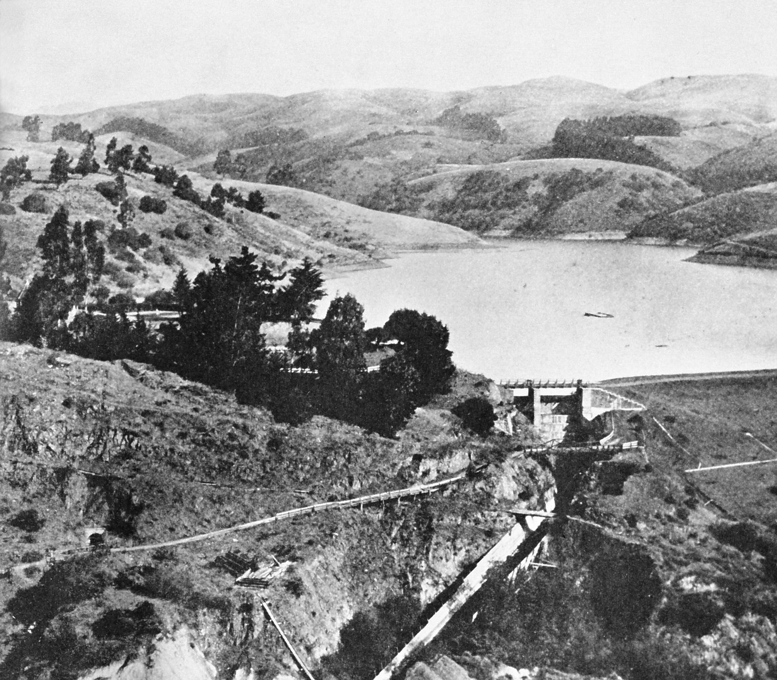 A black and white photo of lake chabot nestled below rolling hills.