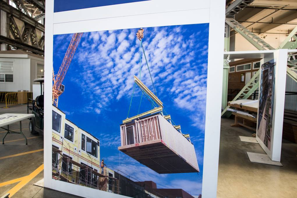 A photo of a completed modular home being lifted by a crane onto a building, at Factory OS in Vallejo on August 6, 2020.