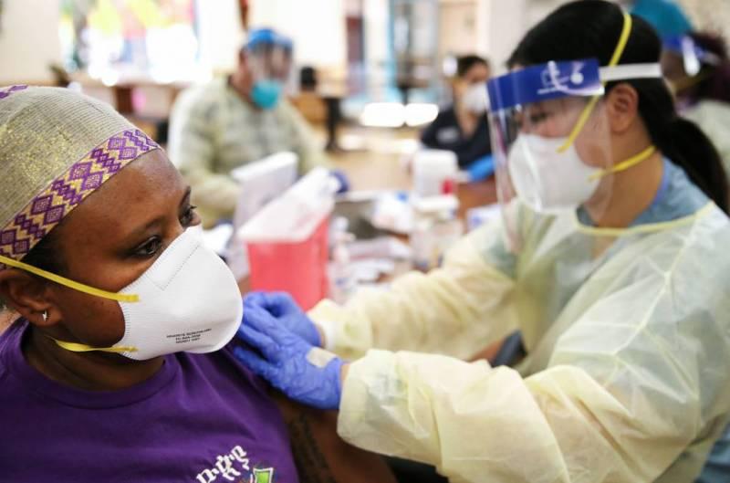 La enfermera Bethlehem Gurmu (izquierda) recibe una dosis de la vacuna contra COVID-19 de Moderna de la enfermera Kathy Luu, como parte de la vacunación masiva del personal del centro de enfermería Ararat en el vecindario de Mission Hills en Los Ángeles el 7 de enero de 2021. Residentes y personal de los centros de atención a largo plazo están en la lista de mayor prioridad de los CDC para las vacunas.