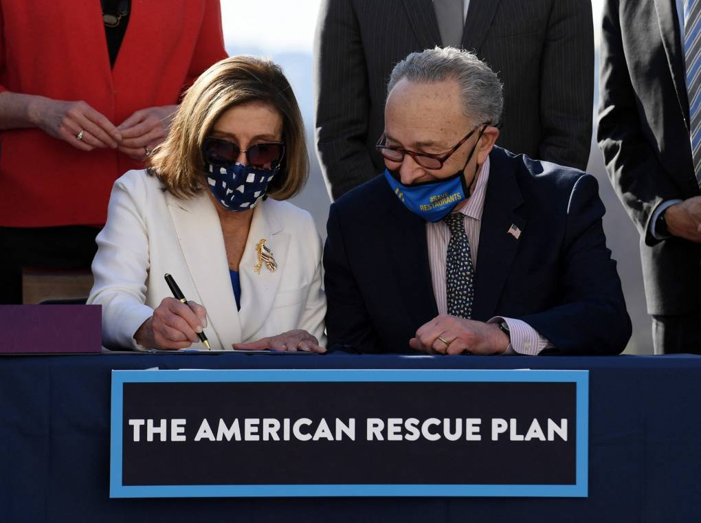 Pelosi and Schumer sitting with masks on, signing American Rescue Plan Act