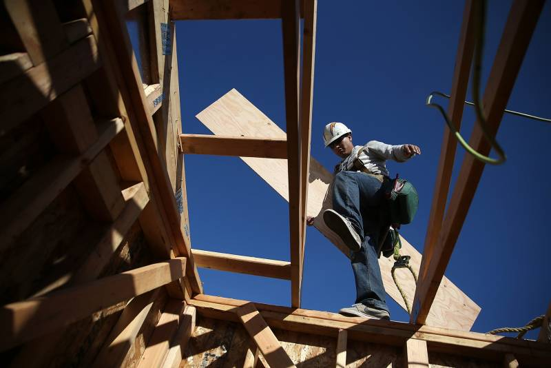 worker carrying lumber precariously on roof of building under construction