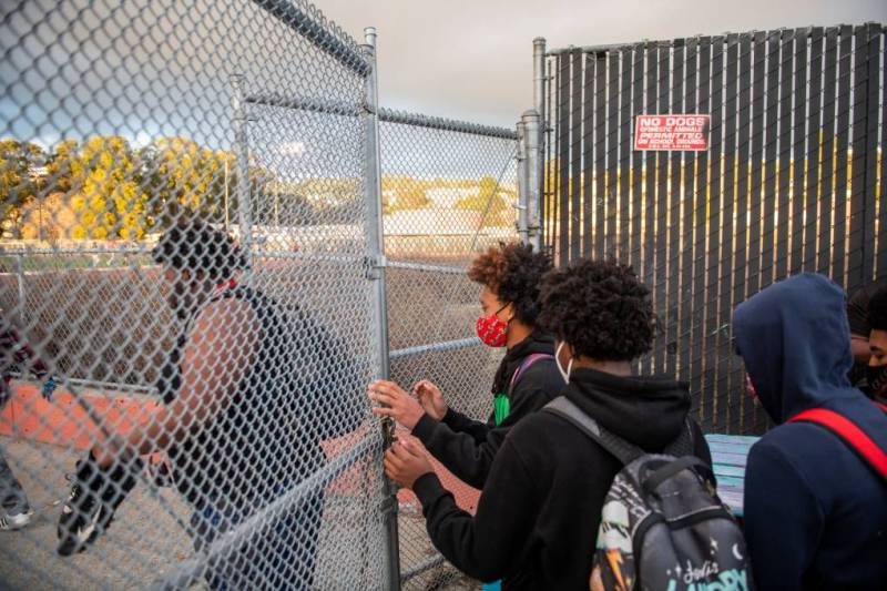 Students wearing masks and backpacks walk through a chain-link fence.