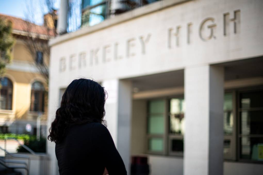 Anonymous Berkeley High student known as 'Faith' standing in front of the high school, back turned