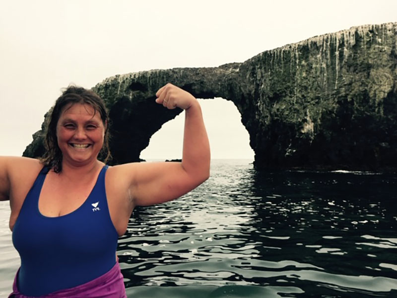 Amy Gubser flexes her arms with ocean and coastline behind her