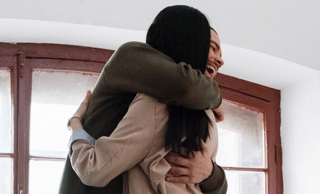 Two people standing in front of a window, hugging