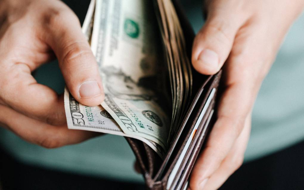 A person's hands touching money in a wallet