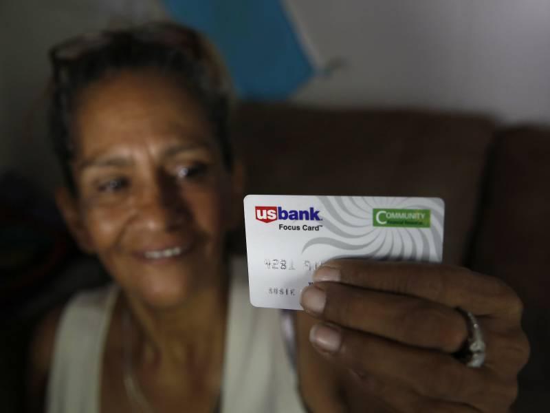 woman UBI recipient smiling, holding debit card