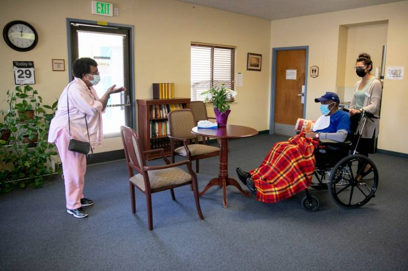 Ouida Dill, left, blows a kiss to her husband, David, at the end of their visit at Lincoln Glen Skilled Nursing Facility in San Jose. David has been a resident at Lincoln Glen for more than four years. For the past year, Ouida visited him almost every every day through a window. Now that Ouida is vaccinated, the couple can see each other indoors again.