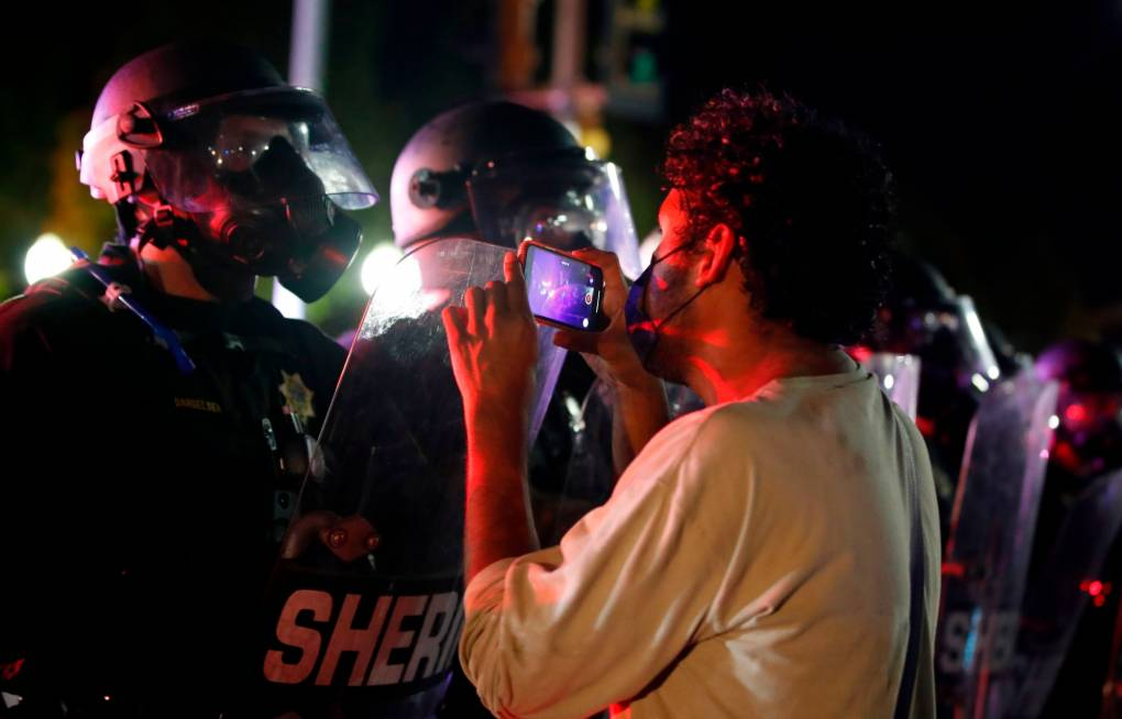 A protester records a video on his cellphone as he faces off with law enforcement outside the County Courthouse during demonstrations against the shooting of Jacob Blake in Kenosha, Wisconsin, on Aug. 25, 2020. Kamil Krzaczynski/AFP via Getty Images