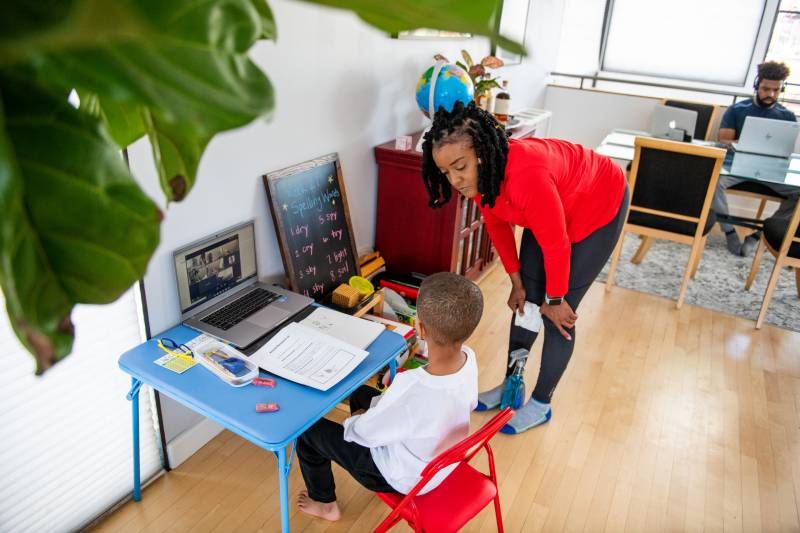 Ryan Austin, artist educator, helps her son Onyx with school through Zoom at their home in Oakland on April 14, 2021.