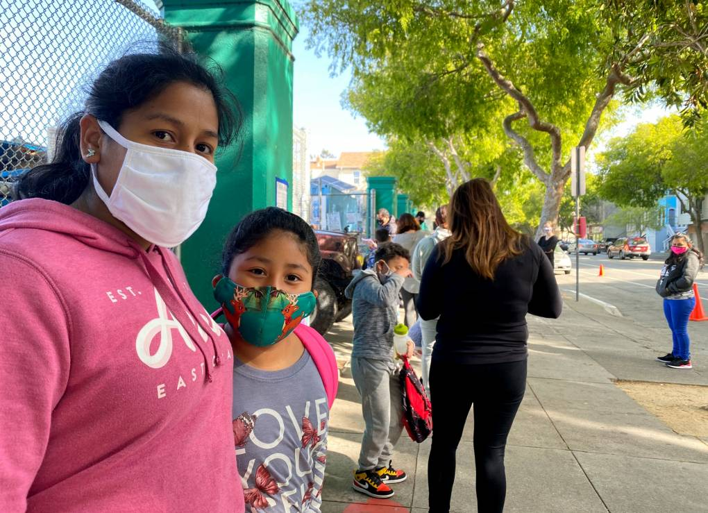 Mom and daughter wearing masks outside school