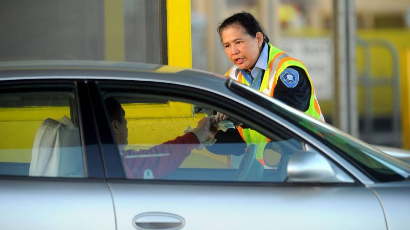 A toll worker taking cash from a driver.