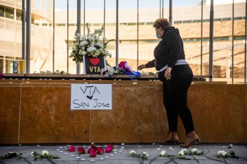 Una mujer coloca una vela en una ofrenda ubicada en las afueras del Ayuntamiento de San José