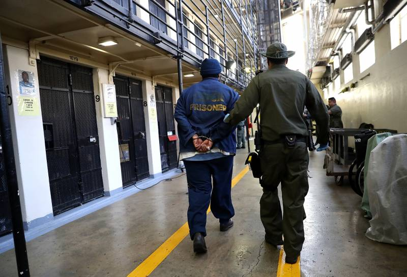 A man in a green uniform and hat leads another in a blue jacket with yellow lettering by his hands shackled behind his back.