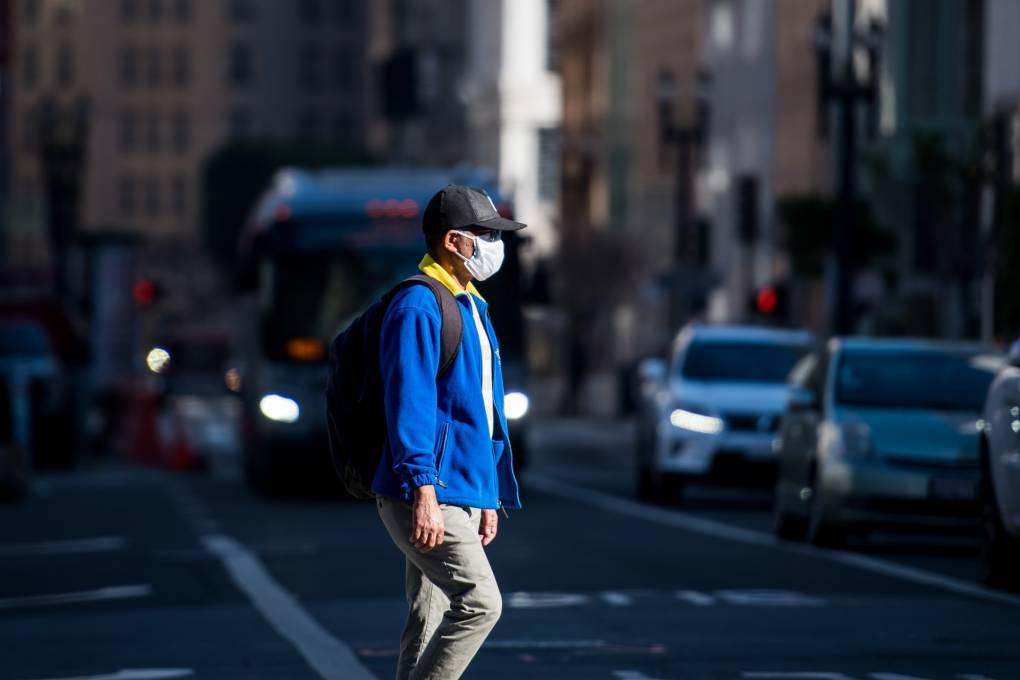 Masked pedestrian crosses SF street