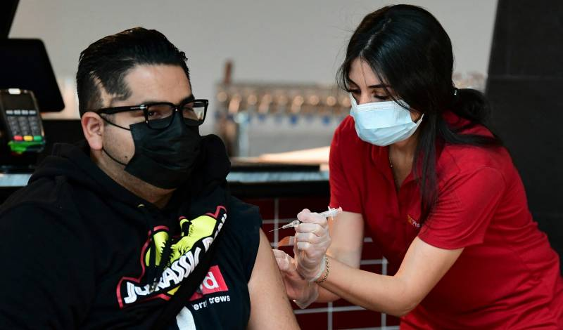 A young man wearing a Jurassic Park hoodie and glasses receives his vaccine from a pharmacist wearing a red shirt.