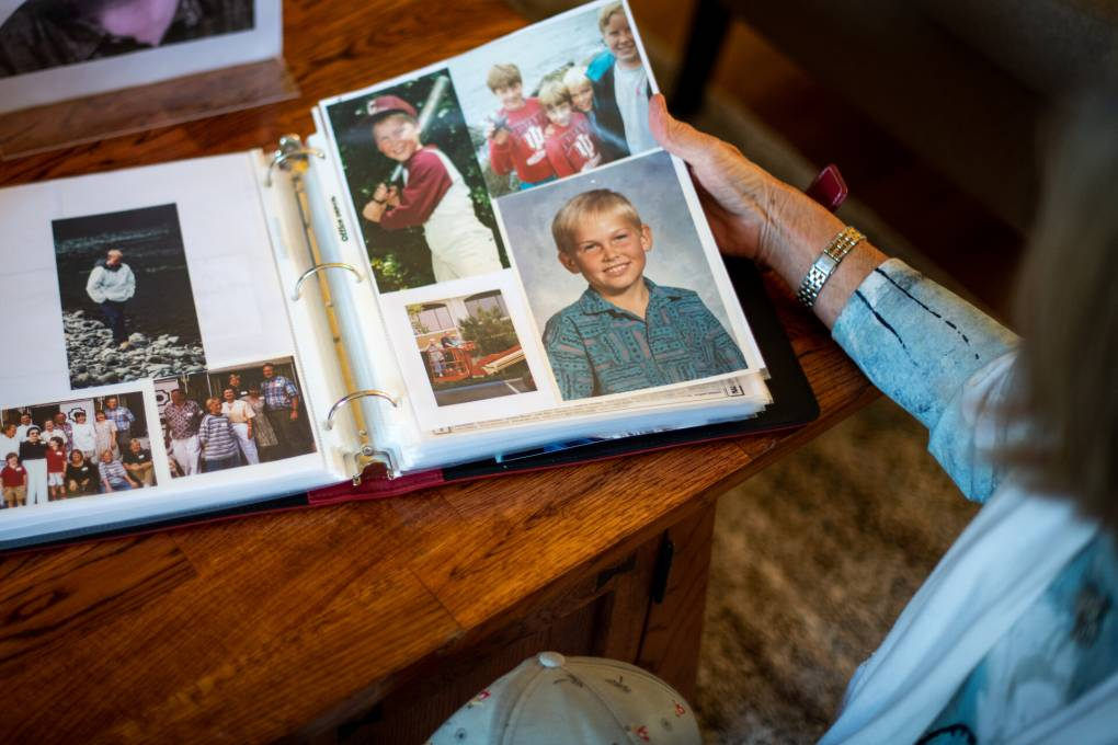 Robin Dosskey looks through childhood photos of her son Kyle at her home in Mountain View on May 12, 2021. Kyle died in 2019 due to a fatal dose of fentanyl. Beth LaBerge/KQED