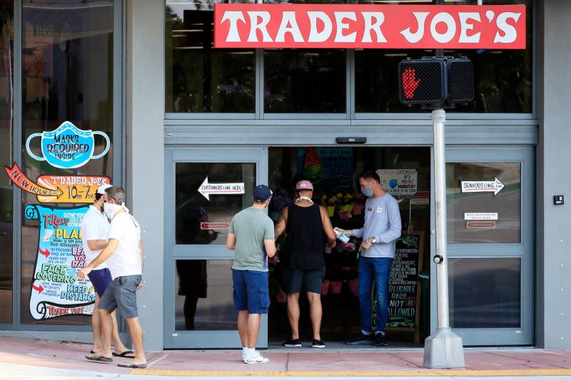 A worker distributes hand sanitizer to customers at a Trader Joe's store. Until June 15, masks will still be required inside stores in California, including national chains like Starbucks, Walmart and Trader Joe's.